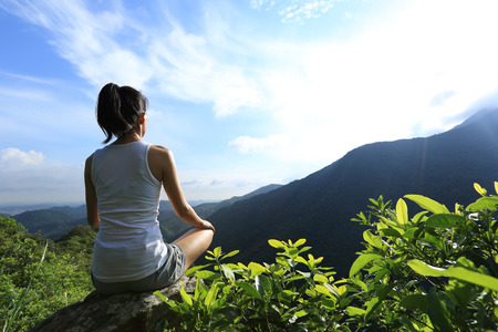 young fitness woman practice yoga at mountain peak rock