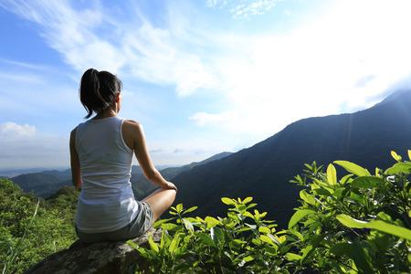 jonge fitness vrouw doe aan yoga op bergtop rots