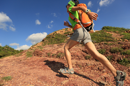 adventure travel: young woman backpacker running on  seaside mountain trail