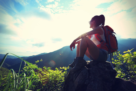 adventure travel: woman backpacker on mountain peak enjoy the view, vintage effect