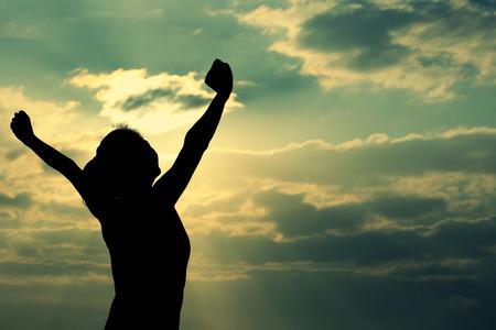 Mujer fuerte confianza brazos abiertos bajo el sol en la playa