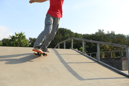 ramp: skateboarder legs riding skateboard at skatepark ramp
