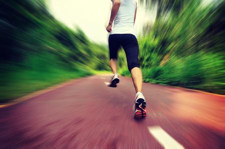 coureur: jeune femme de remise en forme des jambes de coureur courir au sentier de la for�t Banque d'images