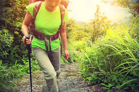 stair climber: young woman backpacker hiking on mountian stairs Stock Photo