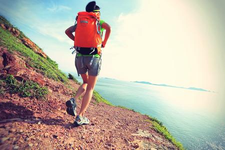 sandal tree: young woman backpacker walking on  seaside mountain trail