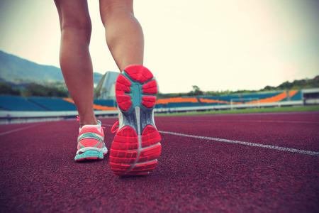 personas corriendo: mujer joven corriendo en la pista, efecto de la vendimia Foto de archivo