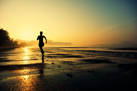 sport silhouette: young healthy lifestyle woman running at sunrise beach Stock Photo