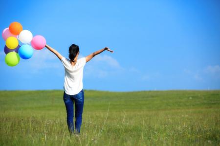 cielos abiertos: mujer asiática joven corriendo y saltando en prado verde con globos de colores