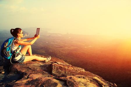 旅行: 女性ハイカーが山の頂上でデジタル タブレットを使用します。