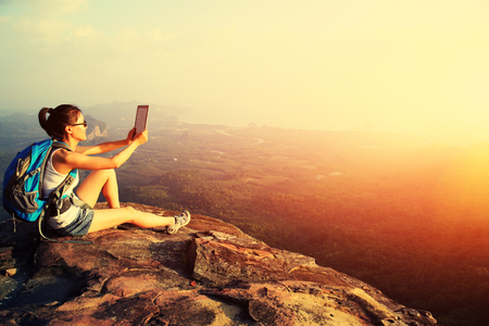 landscape: woman hiker use digital tablet at mountain peak Stock Photo