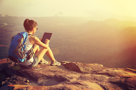 woman hiker use digital tablet at mountain peak Stockfoto