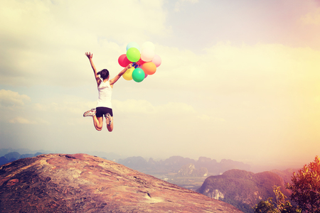 cheering young asian woman jumping on mountain peak rock with colored balloons Archivio Fotografico