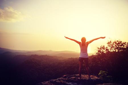 fitness: mulher confiança forte braços abertos sob o nascer do sol no beira-mar Imagens
