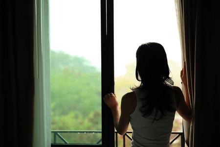 chambre à coucher: fille l'ouverture des rideaux dans une chambre