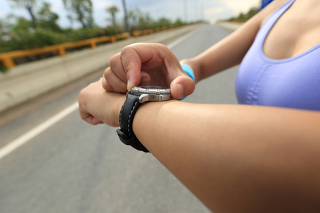 pulse trace: young woman jogger  looking at sports smart watch, checking performance or heart rate pulse trace.  Stock Photo