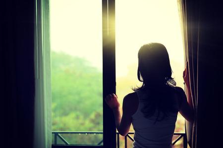 mujer en la cama: niña abriendo las cortinas en un dormitorio