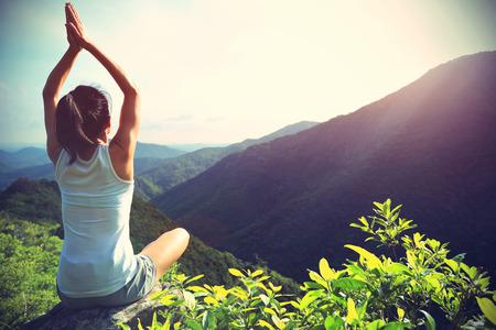 yoga rocks: young fitness woman practice yoga at mountain peak rock, vintage effect Stock Photo