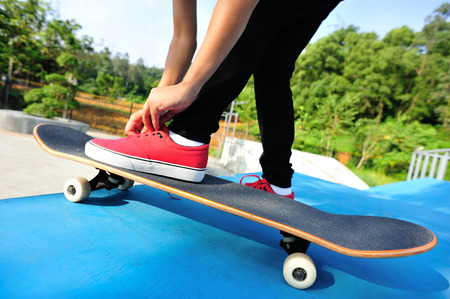 shoelace: skateboarding woman tying shoelace at skatepark