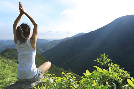 vida sana: Joven mujer la pr�ctica de yoga en el pico de roca de la monta�a Foto de archivo