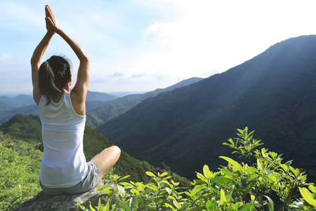 healthy lifestyle: young fitness woman practice yoga at mountain peak rock