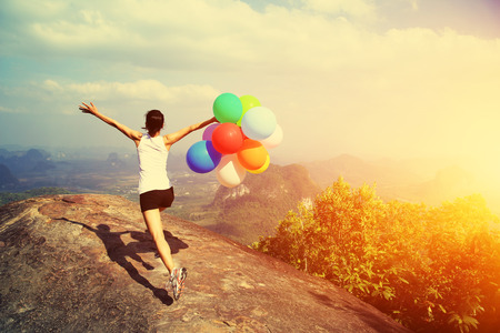 cheering young asian woman running with colored balloons Foto de archivo