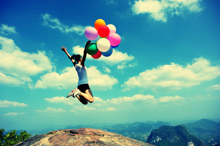 korean woman: cheering young asian woman jumping on mountain peak rock with colored balloons Stock Photo