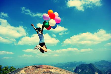 giovane donna asiatica incoraggiante che salta sulla roccia del picco di montagna con i palloni colorati