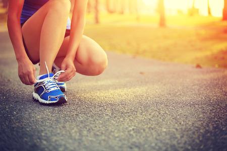 coureur: jeune femme coureur attachant lacets Banque d'images