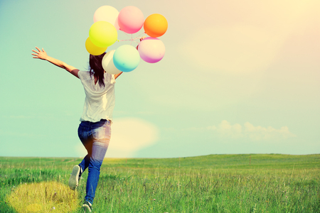 young asian woman running and jumping on green grassland with colored balloons 스톡 콘텐츠