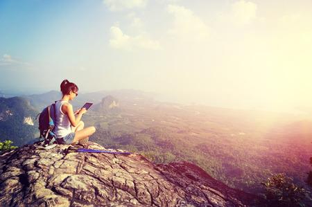 生活方式: 女子徒步旅行者使用數字平板電腦在山峰
