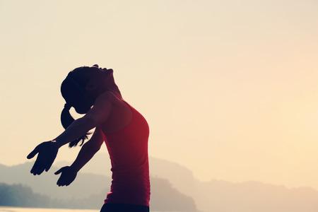 cielos abiertos: mujer joven brazos abiertos bajo la salida del sol en la playa
