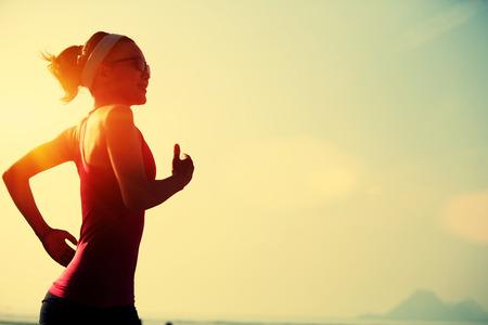 sol radiante: aptitud de la mujer joven que se ejecutan en la playa de la salida del sol