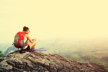 ifestyle: young woman hiker taking photo with smart phone at mountain peak