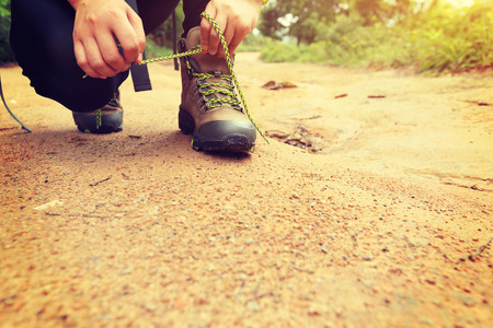 shoelace: woman hiker tying shoelace on forest trail