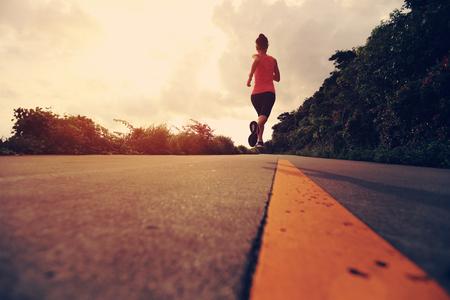 atleta corriendo: Runner atleta que corre en el camino de la playa. Aptitud de la mujer trotar entrenamiento concepto de bienestar.