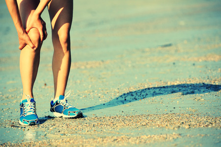 chinese people: woman runner hold her sports injured knee Stock Photo