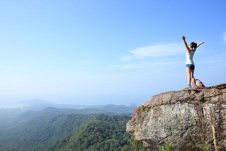 juichen jonge vrouw wandelaar open armen op bergtop Stockfoto