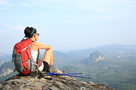hiking: woman hiker enjoy the view at sunset mountain peak cliff