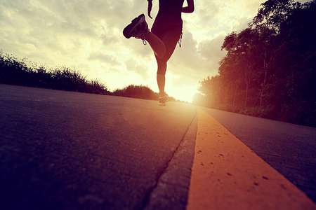 jogging shoes: athlete running at seaside road. woman fitness silhouette sunrise jogging workout wellness concept.