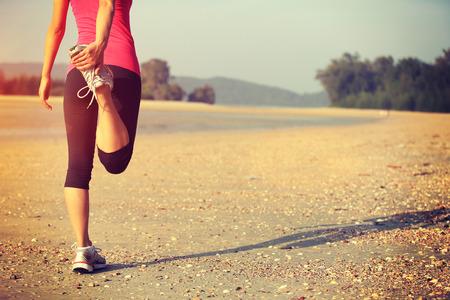 personas trotando: Corredor de la mujer se caliente antes de tomar un trote en la playa Foto de archivo