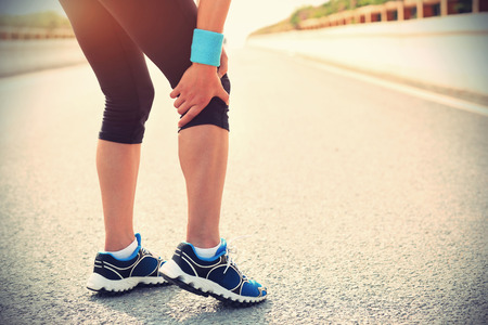 twitch: woman runner hold her injured leg Stock Photo