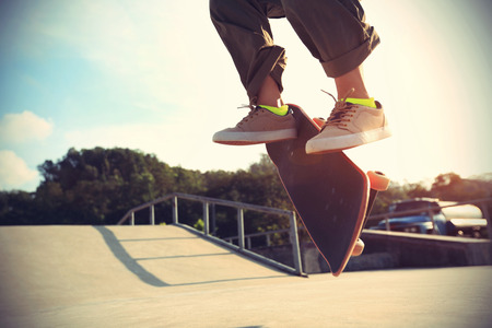 skateboard shoes: skateboarder legs doing a trick ollie at skatepark
