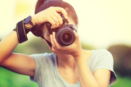 camera lens: young woman photographer taking photo outdoor Stock Photo