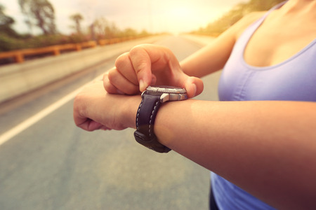 watch city: young woman jogger ready to run set and looking at sports smart watch, checking performance or heart rate pulse trace. Sport and fitness outdoors in city. Stock Photo