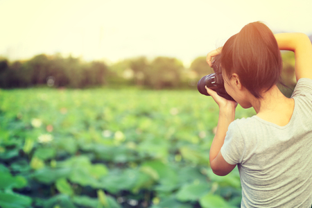 taking photo: young woman photographer taking photo outdoor Stock Photo