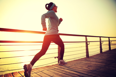 chinese women: young fitness woman runner running at seaside boardwalk Stock Photo
