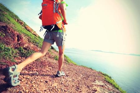 retros: young woman backpacker walking on  seaside mountain trail