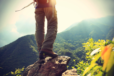rock cliff: woman hiker legs on sunrise mountain peak rock Stock Photo