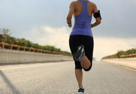 young  cuffs: Runner athlete running on road. woman fitness jogging workout wellness concept.