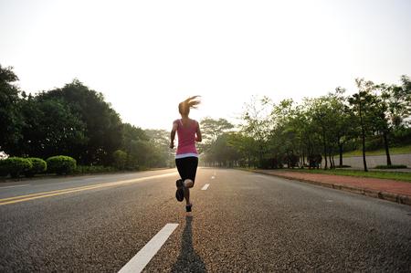 coureur: Runner athl�te qui court � la route. femme de remise en forme lever le jogging entra�nement concept de bien-�tre. Banque d'images